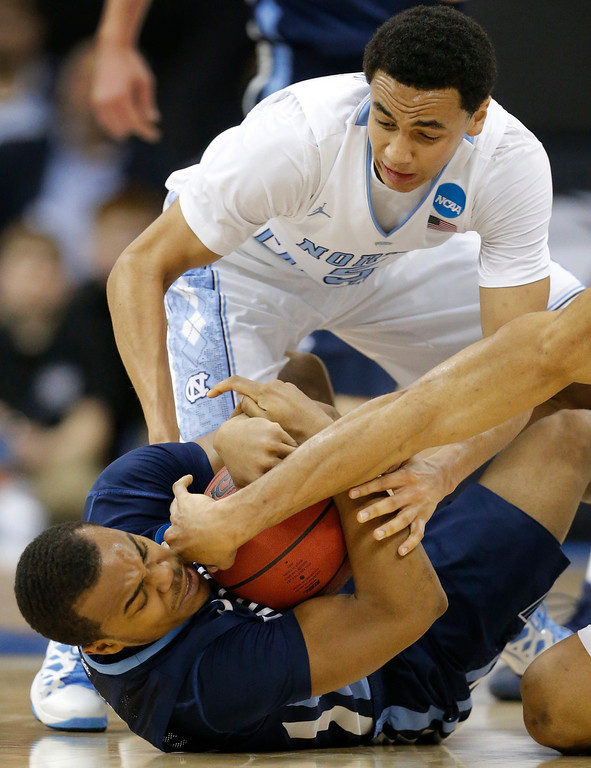 . Villanova guard Tony Chennault, front, gathers a loose ball while covered by North Carolina guard Marcus Paige (5) during the first half of a second-round game in the NCAA college basketball tournament at the Sprint Center in Kansas City, Mo., Friday, March 22, 2013. (AP Photo/Orlin Wagner)