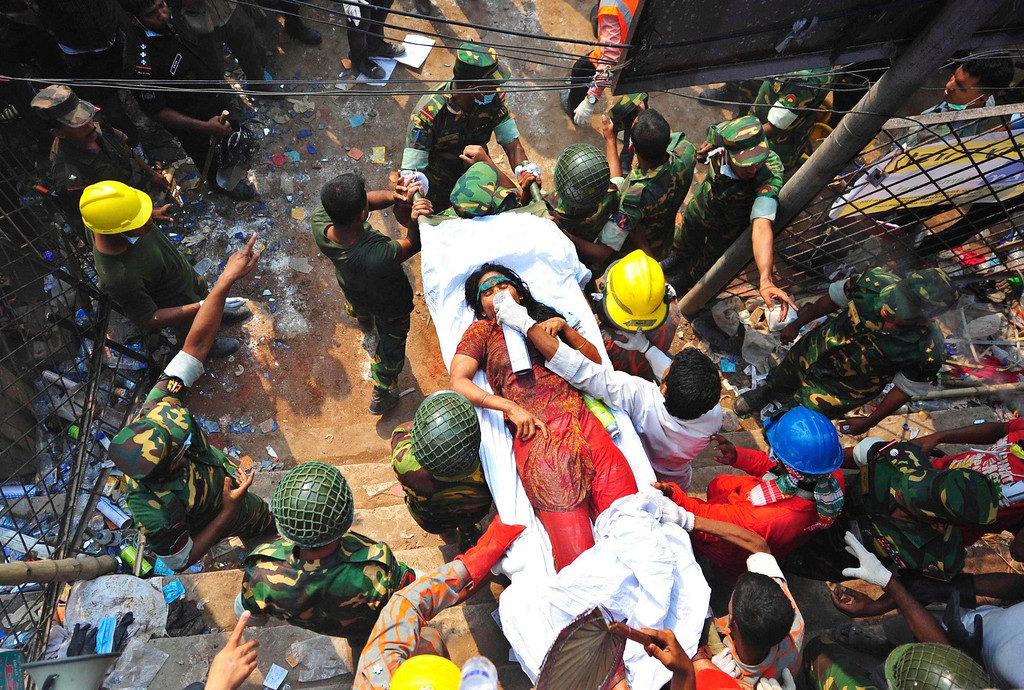 . Rescue workers carry a garment worker, who was pulled alive from the rubble of the collapsed Rana Plaza building, in Savar, 30 km (19 miles) outside Dhaka April 27, 2013. Two factory bosses and two engineers were detained in Bangladesh on Saturday, three days after the collapse of a building where low-cost garments were made for Western brands killed at least 352 people. More were being pulled alive from the rubble at the building, where police said as many as 900 people were still missing in Bangladesh\'s worst ever industrial accident. REUTERS/Stringer