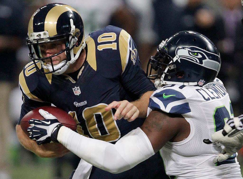 . St. Louis Rams quarterback Kellen Clemens (10) runs against Seattle Seahawks defensive end Chris Clemons (91) during the first half of an NFL football game, Monday, Oct. 28, 2013, in St. Louis. (AP Photo/Tom Gannam)