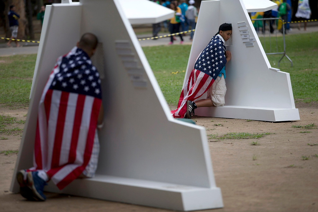 . People wearing U.S. flags kneel at portable confessionals set up in Quinta da Boa Vista park during World Youth Day events in Rio de Janeiro, Brazil, Tuesday, July 23, 2013. The pope is here on a seven-day visit meant to fan the fervor of the faithful around the globe. (AP Photo/Silvia Izquierdo)