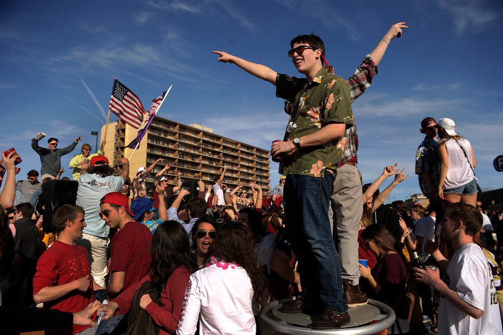 . DENVER, CO. - MARCH 2: Jack Courtney and Kerry DePena Loza danced atop a table as a DJ spun tunes. University of Denver students created a party atmosphere outside Magness Arena Saturday afternoon. DU had both a lacrosse game and a basketball game to keep students busy. The University of Denver men\'s basketball team hosted New Mexico State Saturday afternoon, March 2, 2013. (Photo By Karl Gehring/The Denver Post)