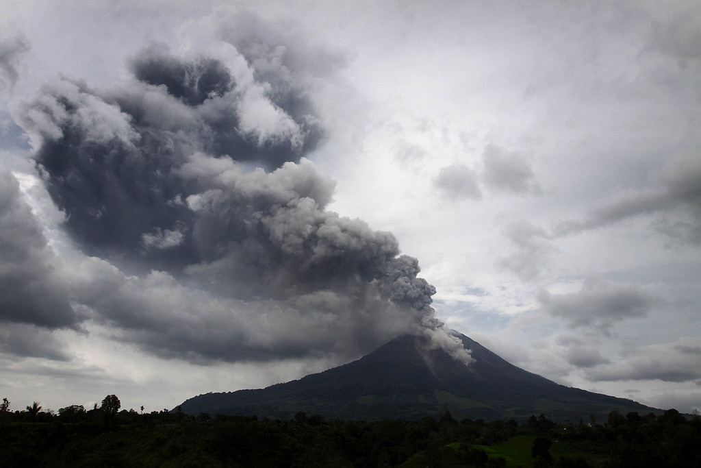 . A giant plume of steam and ash rises from the crater of Mount Sinabung volcano during an eruption as seen from Karo district on Indonesia\'s Sumatra island on November 5, 2013.   AFP PHOTO / KARISHMA TARIGAN/AFP/Getty Images