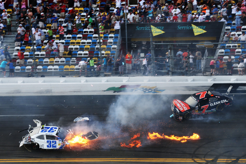 . DAYTONA BEACH, FL - FEBRUARY 23: Kyle Larson, driver of the #32 Clorox Chevrolet, and Regan Smith, driver of the #7 Clean Coal Chevrolet, are involved in an incident at the finish of the NASCAR Nationwide Series DRIVE4COPD 300 at Daytona International Speedway on February 23, 2013 in Daytona Beach, Florida.  (Photo by Matthew Stockman/Getty Images)