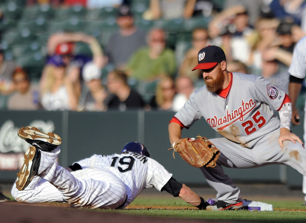 . Colorado Rockies Charlie Blackmon, left, beats the tag by Washington Nationals first baseman Adam LaRoche, right, on a throw to first base by Washington pitcher Jordan Zimmermann in the first inning of a baseball game on Tuesday, July 22, 2014, in Denver. (AP Photo/Chris Schneider)