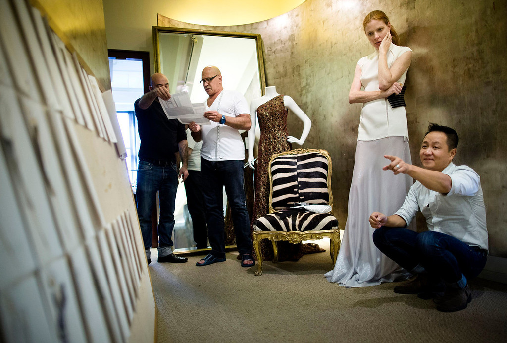 . Fashion designer Carmen Marc Valvo, second from left, consults with his communications director Frank Pulice as Valvo\'s model Taylor Foster, and creative director Il Park, right,  look at fashion drawings in a hallway at Valvo\'s New York studio. Valvo will show his Spring 2014 collection on Sept. 6 at Lincoln Center in New York. (AP Photo/John Minchillo)
