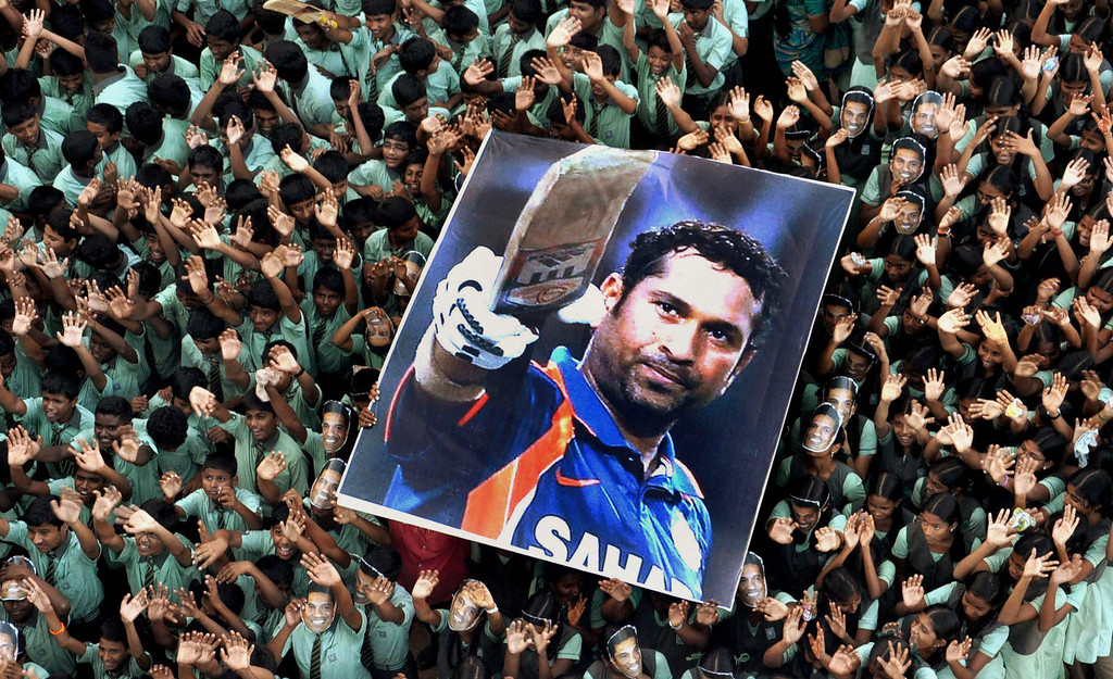 . In this March 16, 2012 file photo, Indian students hold a large poster of Indian cricketer Sachin Tendulkar after Tendulkar batted for his landmark 100th century, at a school in Chennai, southern India. Tendulkar, who had been stuck on 99 centuries for a year, became the first cricketer to score 100 international centuries when he hit to square leg and ran a single against Bangladesh in the Asia Cup. (AP Photo/File) INDIA OUT