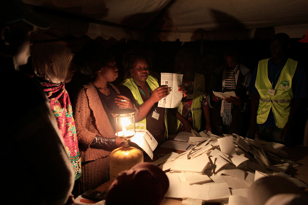 . Officials from the Independent Electoral and Boundaries Commission (IEBC) count ballot papers after voting closed for presidential and parliamentary elections, in Kibera slum, in the capital Nairobi March 4, 2013. At least 15 people were killed in attacks by machete-wielding gangs on Monday as millions of Kenyans voted in the first presidential election since a disputed 2007 poll unleashed weeks of tribal bloodshed. REUTERS/Noor Khamis