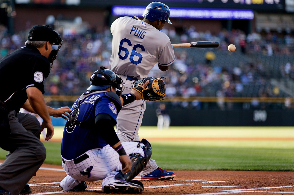 . Yasiel Puig #66 of the Los Angeles Dodgers singles during the first inning as catcher Yorvit Torrealba #8 of the Colorado Rockies looks on at Coors Field on July 2, 2013 in Denver, Colorado.  (Photo by Justin Edmonds/Getty Images)