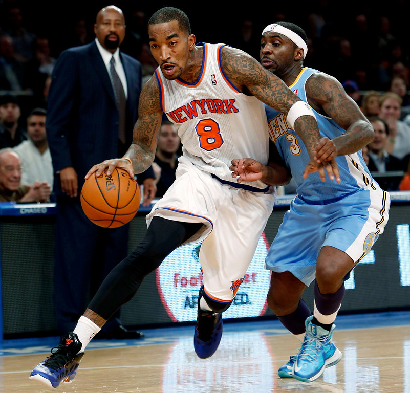 . New York Knicks\' J.R. Smith (8) drives against Denver Nuggets\' Ty Lawson (3) during the first half of an NBA basketball game, Sunday, Dec. 9, 2012, in New York. (AP Photo/Jason DeCrow)