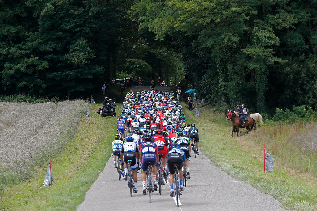 . Three horsewomen pause to watch the pack pass during the eleventh stage of the Tour de France cycling race over 187.5 kilometers (116.5 miles) with start in Besancon and finish in Oyonnax, France, Wednesday, July 16, 2014. (AP Photo/Christophe Ena)