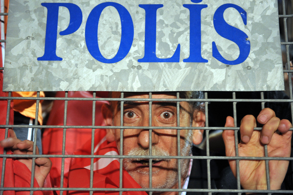". A supporter of Turkish Prime Minister Recep Tayyip Erdogan peers from behind a police barrier upon Erdogan\'s arrival at Ataturk International Airport in Istanbul on June 7, 2013.  Turkey\'s Islamic-rooted government apologised to wounded protestors and said it had ""learnt its lesson\"" after days of mass street demonstrations that have posed the biggest challenge to Prime Minister Recep Tayyip Erdogan\'s decade in office. Turkish police had on June 1 begun pulling out of Istanbul\'s iconic Taksim Square, after a second day of violent clashes between protesters and police over a controversial development project. What started as an outcry against a local development project has snowballed into widespread anger against what critics say is the government\'s increasingly conservative and authoritarian agenda.  OZAN KOSE/AFP/Getty Images"