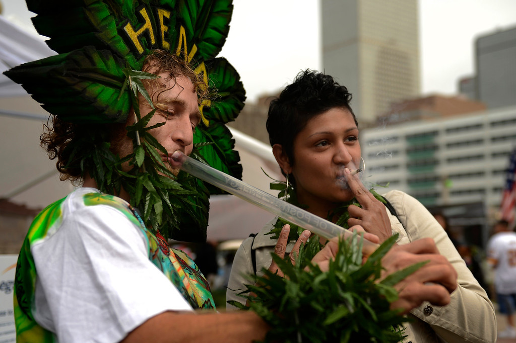. Henry Hemp lighting up with Dreseta Anderson from Oklahoma that came for the weekend of the annual 420 Rally at Civic Center Park in downtown Denver April 20, 2013 Denver, Colorado. (Photo By Joe Amon/The Denver Post)