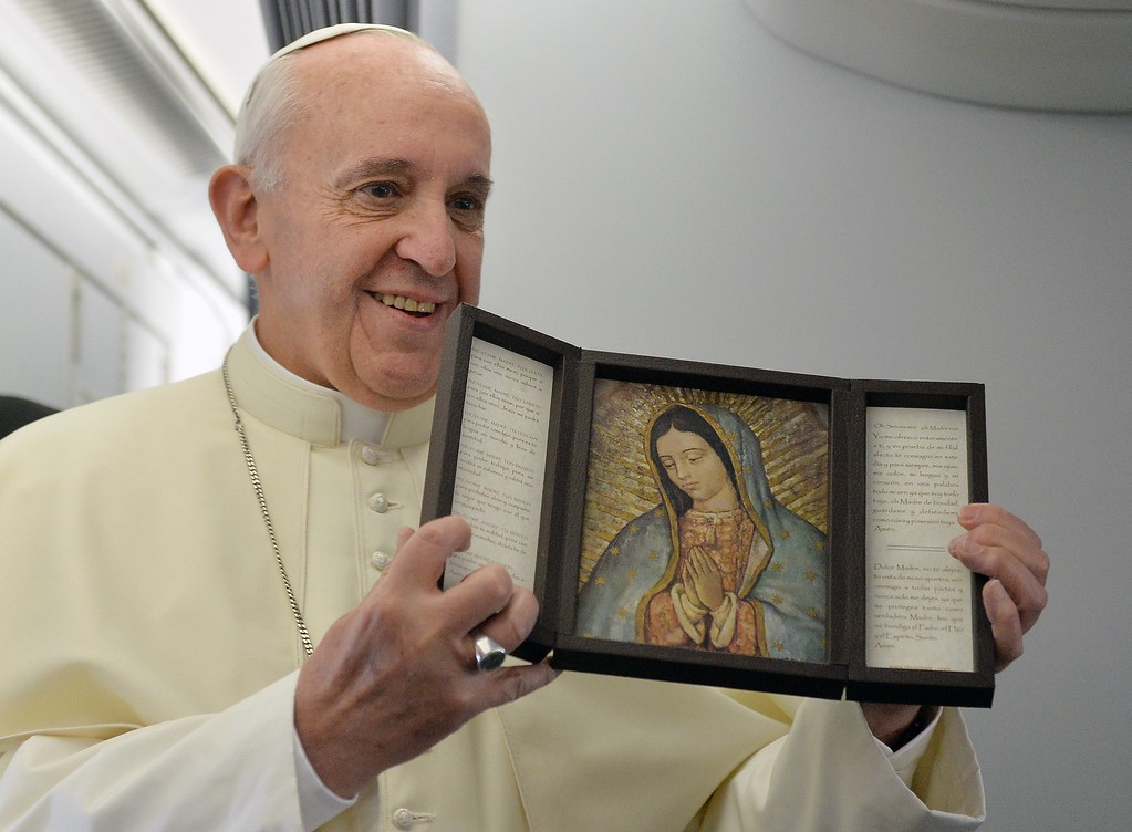 . Pope Francis shows an image of Our Lady of Guadalupe --a gift from a journalist of the papal flight-- upon arrival in Rio de Janeiro on July 22, 2013.   AFP PHOTO/LUCA ZENNARO/POOL