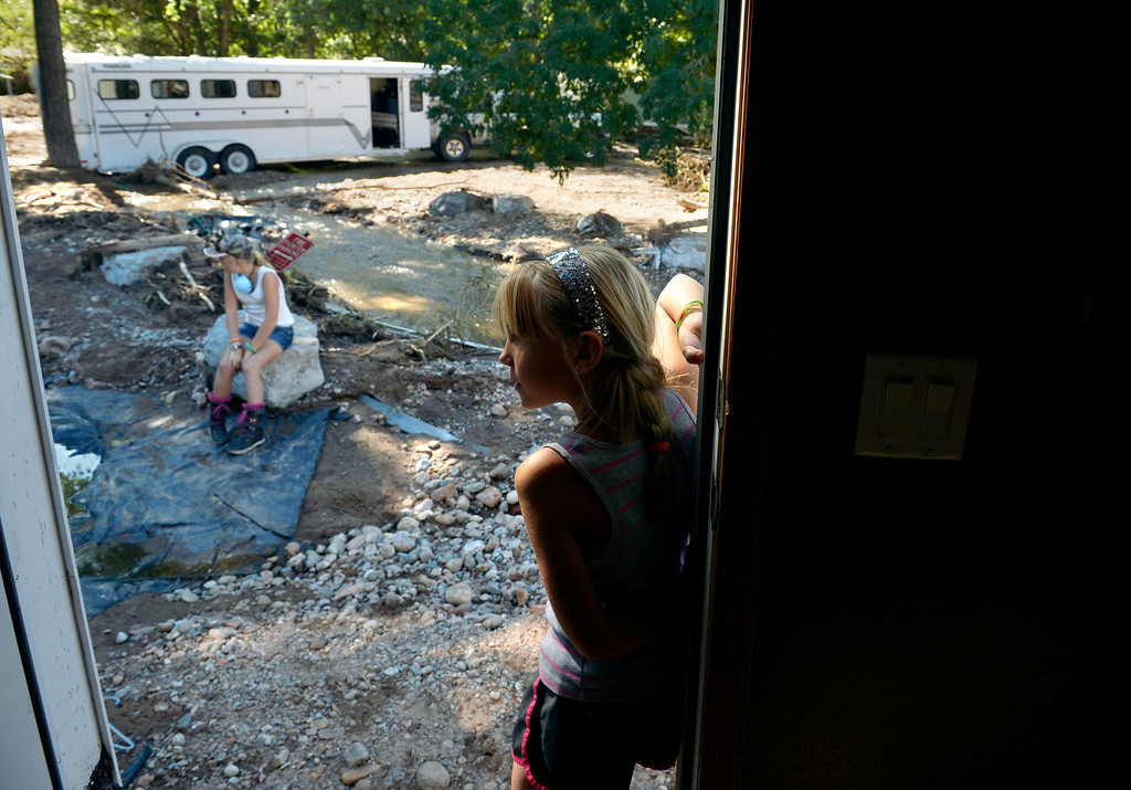 ". (l-r) Serena Koester and her sister Sam look over the yard outside their home in Lyons, CO September 20, 2013. Their father Scott Koester  expects that the home will be condemned after the recent flooding. He said, ""we\'ve been here 10 years now and it\'s all gone. I don\'t know how you\'d save this house.\""  Friday was the second day residents were allowed to return to their homes.  (Photo By Craig F. Walker / The Denver Post)"