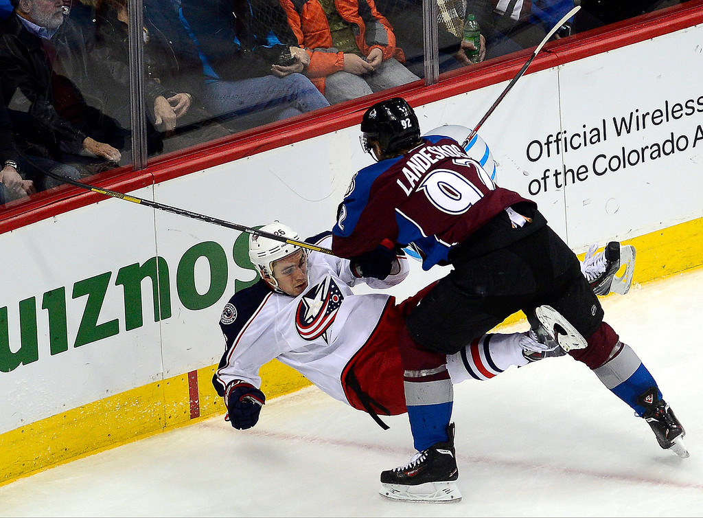 . Gabriel Landeskog (92) of the Colorado Avalanche checks Corey Tropp (26) of the Columbus Blue Jackets during the second period. The Colorado Avalanche hosted the Columbus Blue Jackets at the Pepsi Center on Tuesday, December 31, 2013. (Photo by AAron Ontiveroz/The Denver Post)