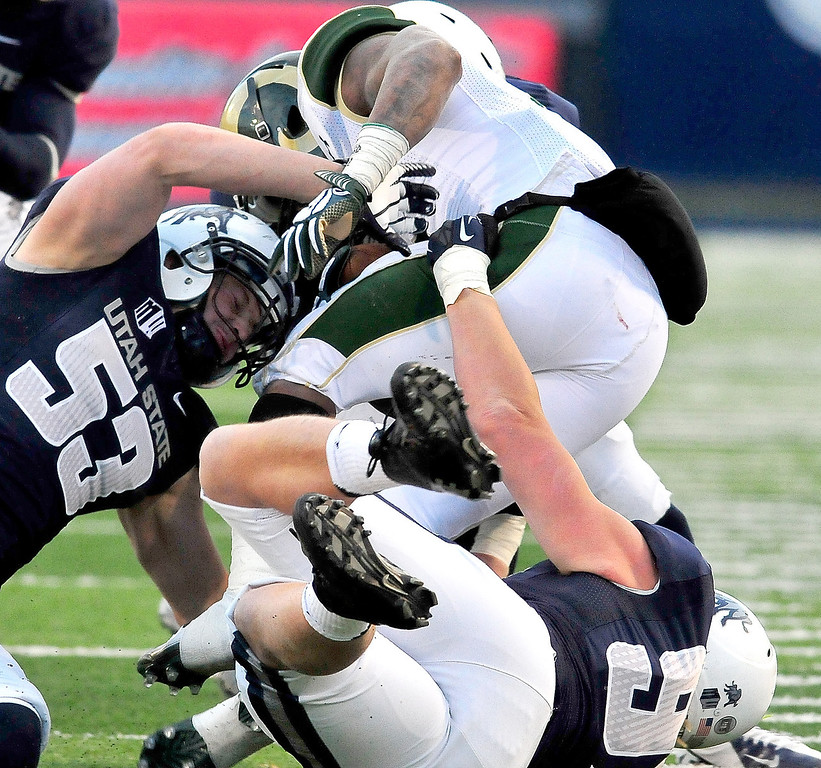 . Colorado State\'s Kapri Bibbs gets tackled by Utah State\'s Zach Vigil (53) and Jordan Nielsen during an NCAA college football game, Saturday, Nov. 23, 2013, in Logan, Utah. Utah State won 13-0. (AP Photo/Herald Journal, John Zsiray)