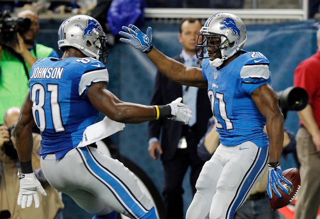 . Detroit Lions wide receiver Calvin Johnson (81) congratulates running back Reggie Bush after Bush\'s 14-yard touchdown during the first quarter of an NFL football game against the Baltimore Ravens in Detroit, Monday, Dec. 16, 2013. (AP Photo/Duane Burleson)