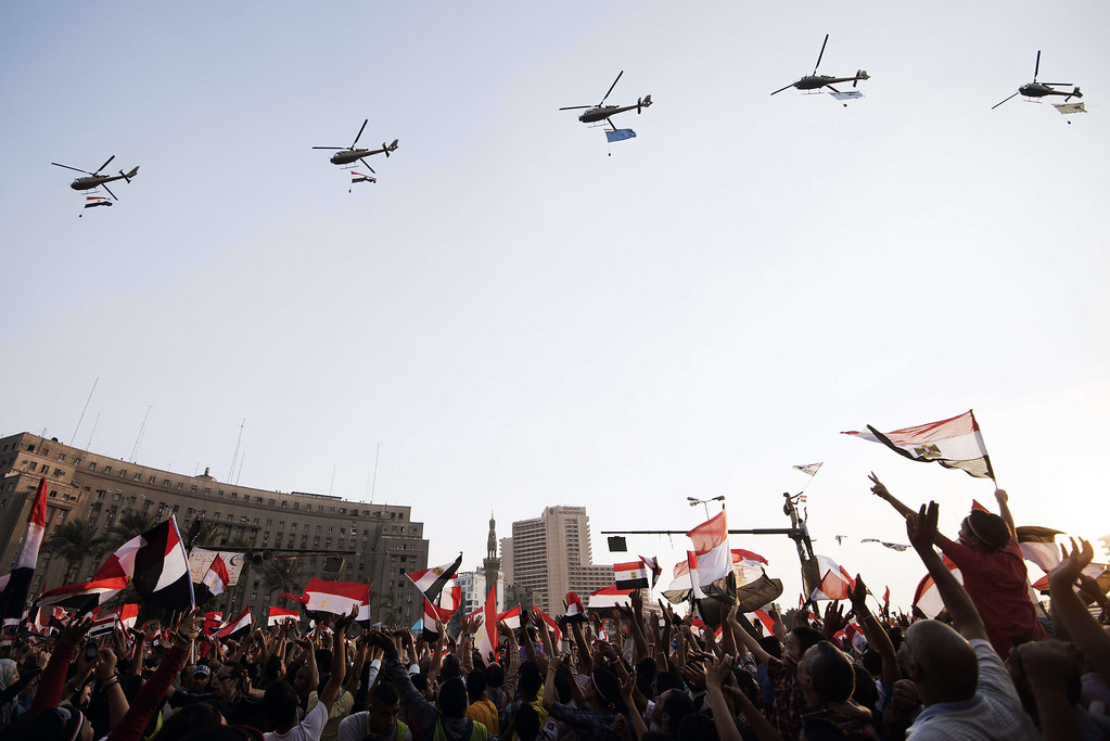 ". Egyptian people wave the national flag as army helicopters fly above Egypt\'s landmark Tahrir square on July 4, 2013. Egypt\'s Muslim Brotherhood, from which ousted president Mohamed Morsi hails, denounced a new ""police state\"" after the arrest of Islamist leaders and the closure of satellite channels. GIANLUIGI GUERCIA/AFP/Getty Images"