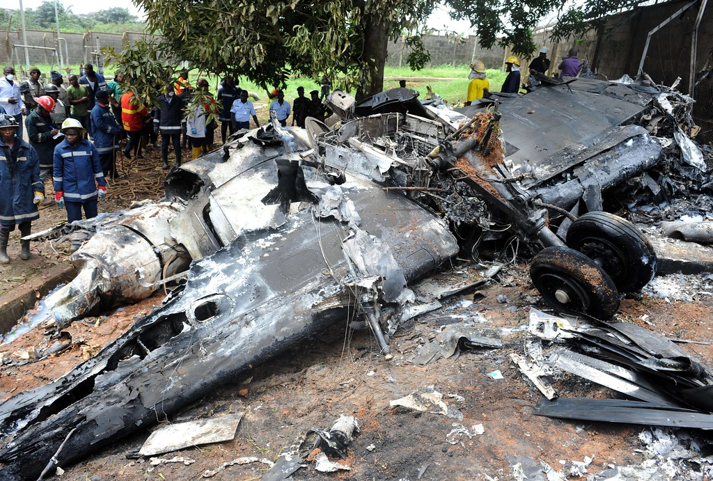 . Nigerian rescue workers gather around the wreckage of an Associated Airlines plane that crash-landed at Sahara Airport shortly after takeoff in Lagos on October 3, 2013. T AFP PHOTO/ PIUS UTOMI EKPEI /AFP/Getty Images