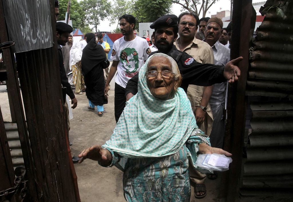 . An elderly Pakistani woman leaves a polling station after casting her ballot in Lahore, Pakistan, Saturday, May 11, 2013. Defying the danger of militant attacks, Pakistanis streamed to the polls Saturday for a historic vote pitting a former cricket star against a two-time prime minister and an unpopular incumbent. But bombings that killed and wounded dozens underlined the risks many people took just casting their ballots. (AP Photo/K.M. Chaudary)