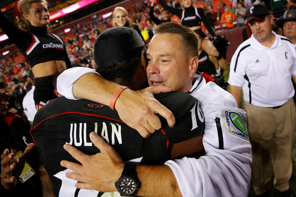 . LANDOVER, MD - SEPTEMBER 29: Head coach Butch Jones of the Cincinnati Bearcats hugs receiver Damon Julia #16 after his team defeated the Virginia Tech Hokies 27-24 at FedExField on September 29, 2012 in Landover, Maryland. (Photo by Jonathan Ernst/Getty Images)