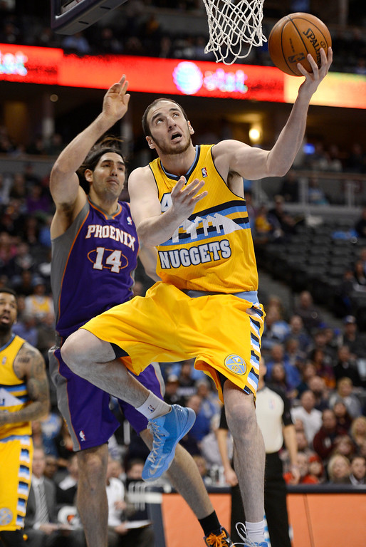 . Kosta Koufos (41) of the Denver Nuggets drives under the basket past Luis Scola (14) of the Phoenix Suns during the first quarter April 17,  2013 at Pepsi Center. (Photo By John Leyba/The Denver Post)