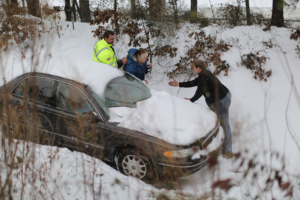 . Jacqueline Helton is taken to safety by roadside assistance personnel after her car slid down an embankment on All-American Highway during a winter storm Wednesday, Feb. 12, 2014. Helton was stuck in the embankment for about two hours. (AP Photo/The Fayetteville Observer, Jill Knight)