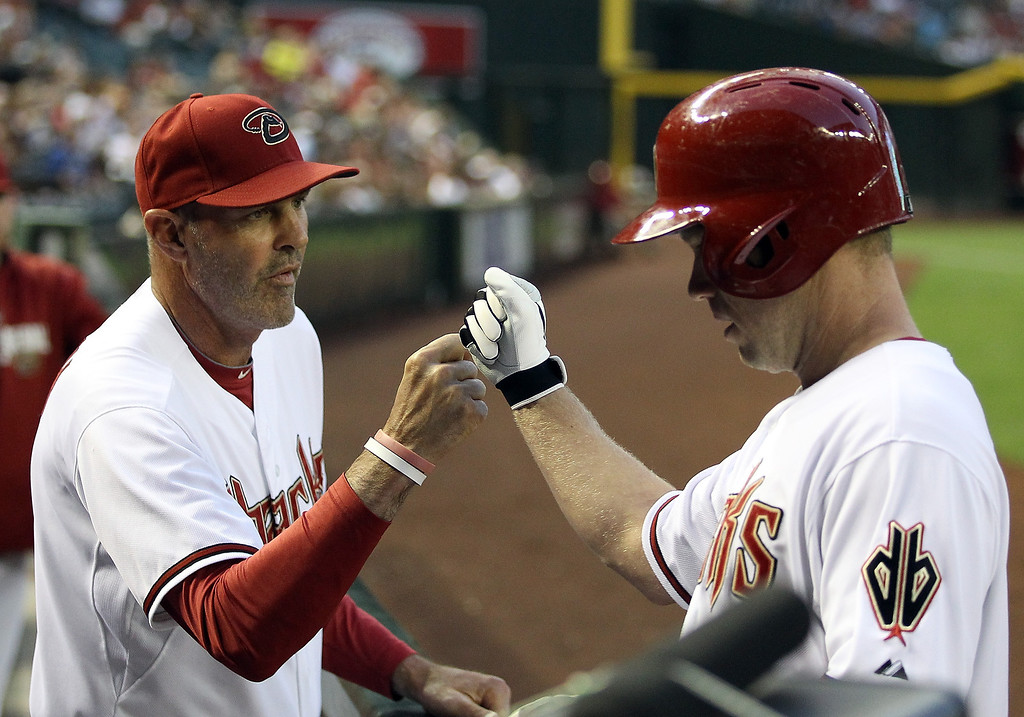 . Manager Kirk Gibson #23 of the Arizona Diamondbacks high fives Aaron Hill #2 after Hill scored a second inning run against the Colorado Rockies during the MLB game at Chase Field on April 29, 2014 in Phoenix, Arizona.  (Photo by Christian Petersen/Getty Images)