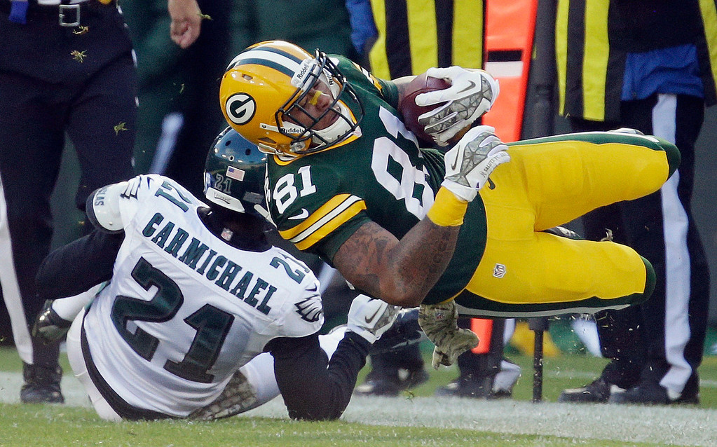 . Green Bay Packers\' Andrew Quarless is tripped up by Philadelphia Eagles\' Roc Carmichael (21) after a catch during the first half of an NFL football game Sunday, Nov. 10, 2013, in Green Bay, Wis. (AP Photo/Mike Roemer)