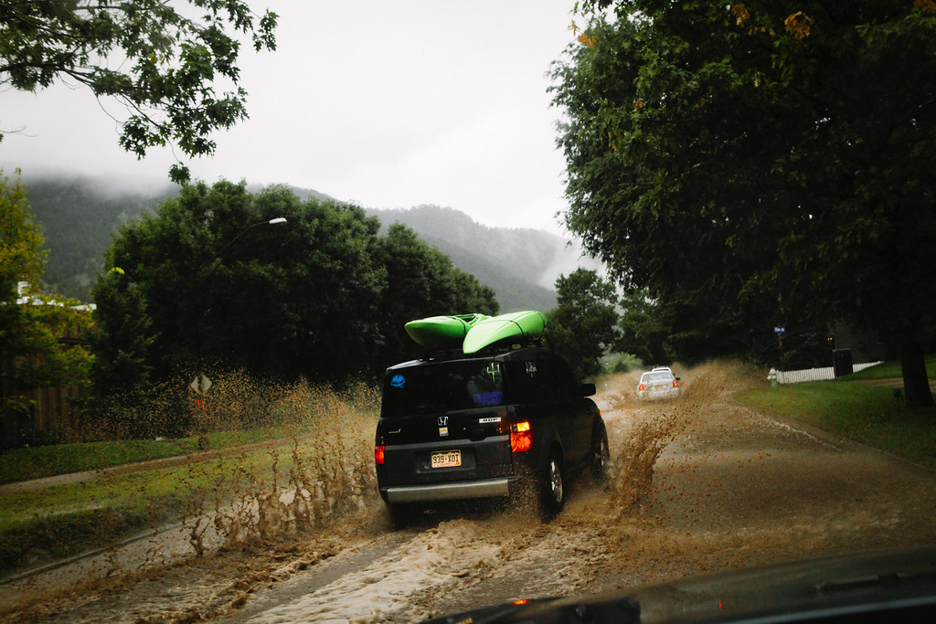. BOULDER, CO - SEPTEMBER 12: A car with kayaks on the roof drives up Canyon Boulevard, which runs parallel to Boulder Creek September 12, 2013 in Boulder, Colorado. An estimated 6-10 inches of rain fell in 12-18 hours and more is expected throughout the day. Flash flood sirens warned people to stay away from Boulder Creek and seek higher ground.  (Photo by Dana Romanoff/Getty Images)