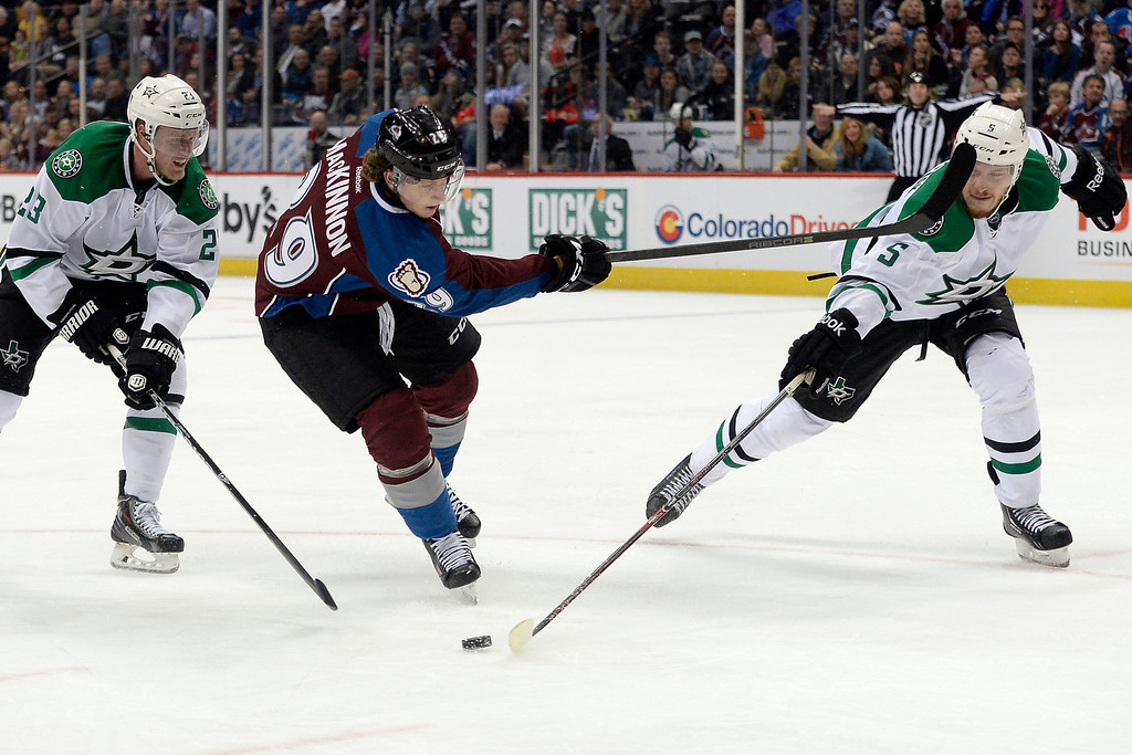 . DENVER, CO - DECEMBER 16: Colorado Avalanche center Nathan MacKinnon (29) takes a shot as Dallas Stars defenseman Jamie Oleksiak (5) and defenseman Kevin Connauton (23) defend during the third period of the Avs\' 6-2 win. The Colorado Avalanche hosted the Dallas stars at the Pepsi Center. (Photo by AAron Ontiveroz/The Denver Post)
