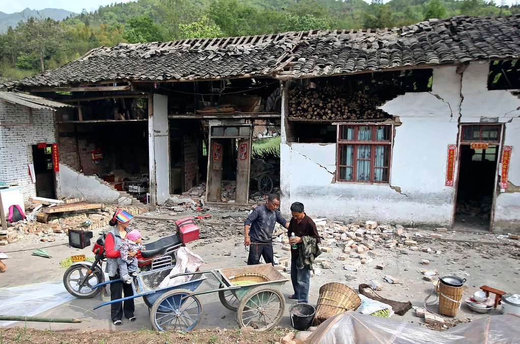 . People stand outside a damaged house after a strong 6.6 magnitude earthquake hit, at Longmen village, Lushan county, Ya\'an, Sichuan province April 20, 2013. The earthquake hit a remote, mostly rural and mountainous area of southwestern China\'s Sichuan province on Saturday, killing at least 102 people and injuring about 2,200 close to where a big quake killed almost 70,000 people in 2008.  REUTERS/Stringer
