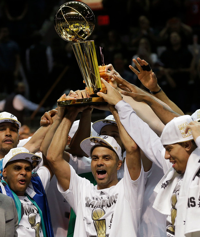 . San Antonio Spurs guard Tony Parker lifts  the Larry O\'Brien NBA Championship Trophy after Game 5 of the NBA basketball finals on Sunday, June 15, 2014, in San Antonio. The Spurs won the NBA championship 104-87. (AP Photo/David J. Phillip)