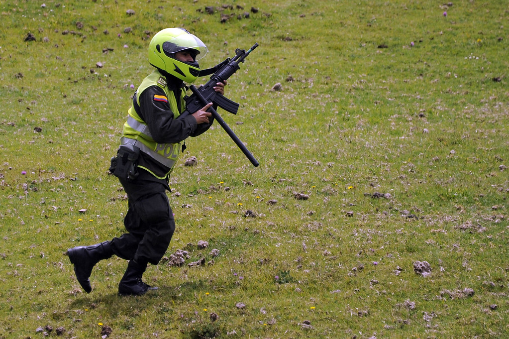 . A Colombian police officer takes position during clashes with farmers at a road blockade in La Calera, Cundinamarca department, on August 23, 2013. A five-day-old farmworkers\' protest in Colombia claimed its first fatality Friday when a man on a motorcycle crashed and died at a roadblock, police said Friday. Since the protests began Monday, farmworkers have closed roads at dozens of points in across the country, blocking the passage of cargo trucks and other vehicles from makeshift camps erected on sides of roads.  EITAN ABRAMOVICH/AFP/Getty Images