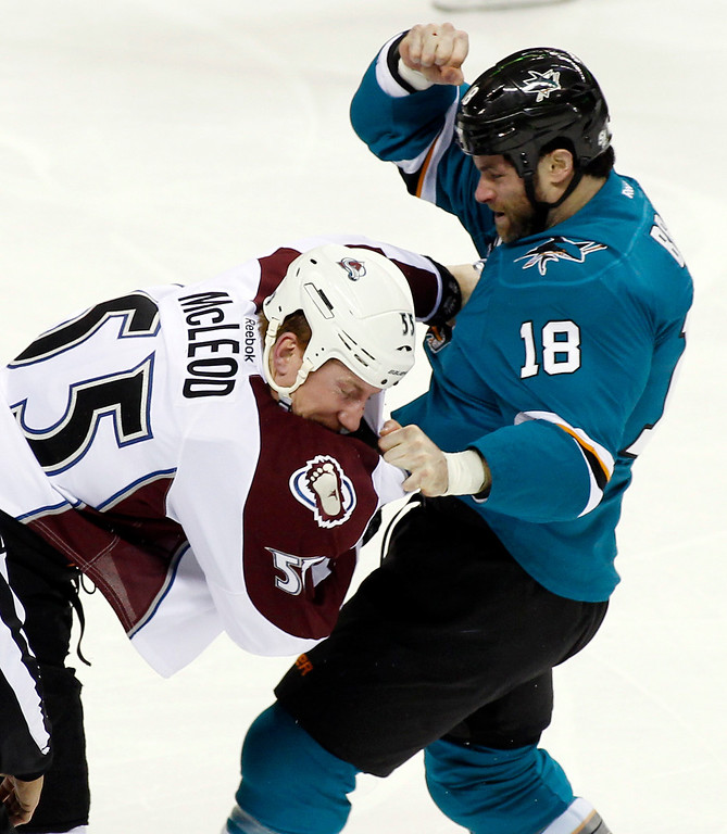 . San Jose Sharks\' Mike Brown, right, fights with Colorado Avalanche\'s Cody McLeod during the first period of an NHL hockey game, Monday, Dec. 23, 2013, in San Jose, Calif. (AP Photo/George Nikitin)