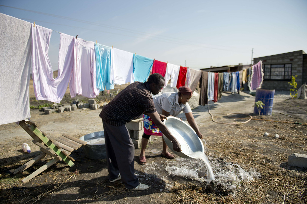 . A miner and his wife wash clothes on July 9, 2013 in the Nkaneng shantytown next to the platinum mine, run by British company Lonmin, in Marikana. On August 16, 2012, police at the Marikana mine open fire on striking workers, killing 34 and injuring 78, during a strike was for better wages and living conditions. Miners still live in dire conditions despite a small wage increase.  ODD ANDERSEN/AFP/Getty Images