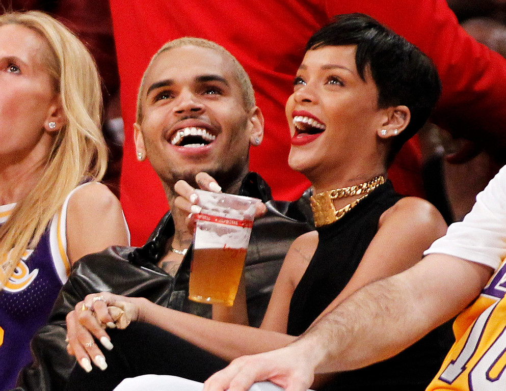 . Recording artists Chris Brown (L) and Rihanna laugh together while sitting courtside at the NBA basketball game between the New York Knicks and Los Angeles Lakers in Los Angeles December 25, 2012. REUTERS/Danny Moloshok