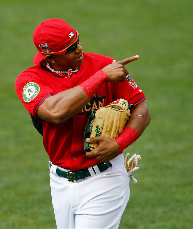 . American League outfielder Yoenis Cespedes, of the Oakland Athletics, runs on the field during batting practice for the MLB All-Star baseball game, Monday, July 14, 2014, in Minneapolis. (AP Photo/Paul Sancya)
