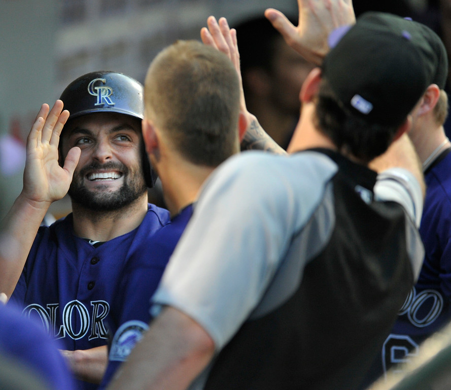 . Colorado Rockies\' Michael McKenry celebrates with teammates in the dugout after scoring on a Charlie Culberson double during the second inning of a baseball game against the Chicago Cubs in Chicago, Wednesday, July 30, 2014. (AP Photo/Paul Beaty)