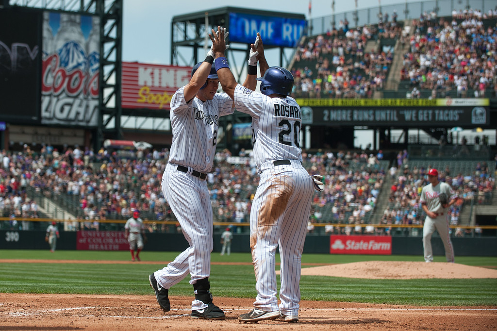 . DENVER, CO - JUNE 15:  Tyler Colvin #21 and Wilin Rosario #20 of the Colorado Rockies celebrate a first inning 2-run Colvin home run off of Jonathan Pettibone #44 of the Philadelphia Phillies  at Coors Field on June 15, 2013 in Denver, Colorado.  (Photo by Dustin Bradford/Getty Images)