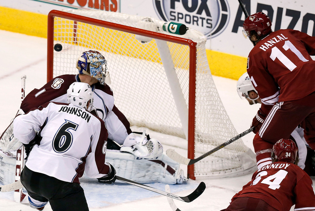 . Phoenix Coyotes\' Martin Hanzal (11), of the Czech Republic, scores a goal against Colorado Avalanche\'s Semyon Varlamov (1), of Russia, as Avalanche\'s Erik Johnson (6) and Coyotes\' Tim Kennedy (34) look on during the third period of an NHL hockey game Thursday, Nov. 21, 2013, in Glendale, Ariz.  The Avalanche defeated the Coyotes 4-3. (AP Photo/Ross D. Franklin)