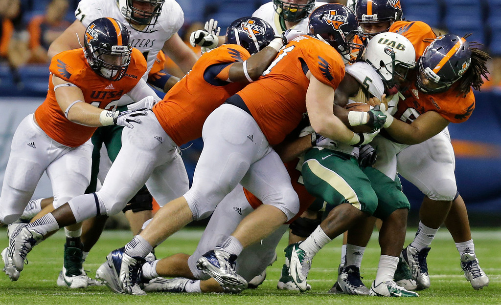 . UAB\'s Darrin Reaves (5) is hit by a wall of UTSA defenders during the second half of an NCAA college football game, Saturday, Oct. 26, 2013, in San Antonio. UTSA won 52-31. (AP Photo/Eric Gay)