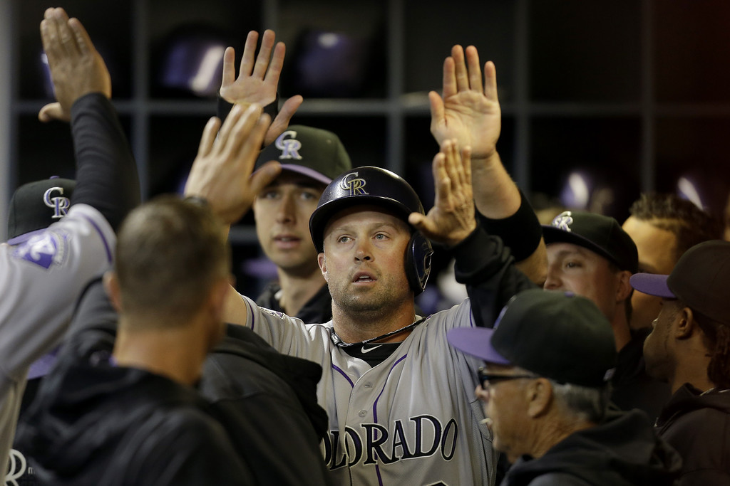 . MILWAUKEE, WI - APRIL 2: Michael Cuddyer #3 of the Colorado Rockies celebrates in the dugout after getting hit home by Chris Nelson in the top of the first inning against the Milwaukee Brewers at Miller Park on April 2, 2013 in Milwaukee, Wisconsin. (Photo by Mike McGinnis/Getty Images)