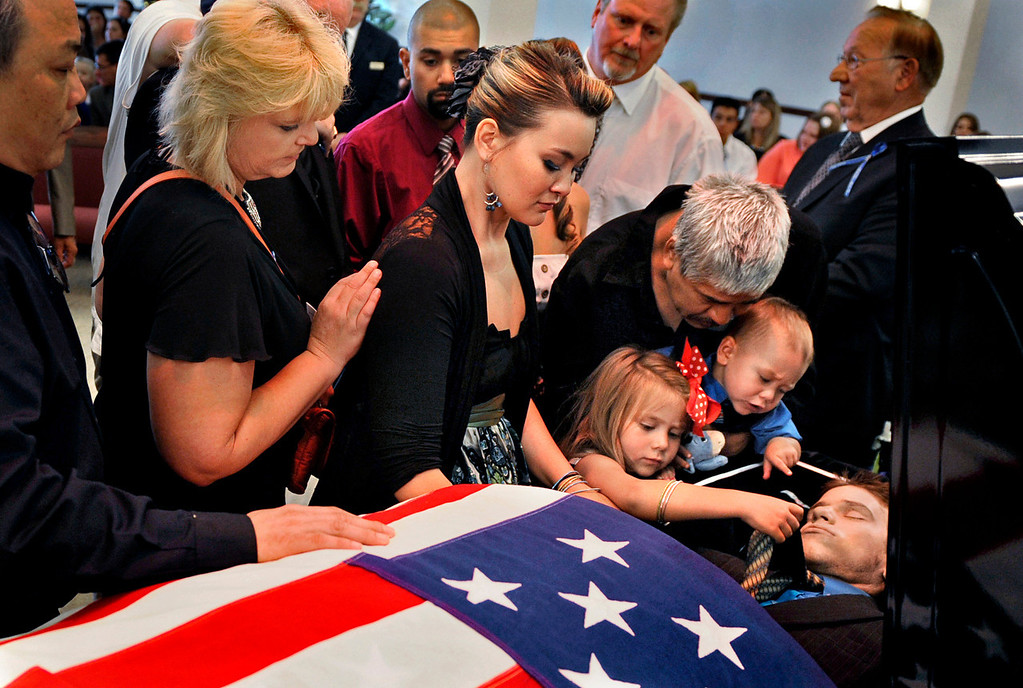 """. Chantel Blunk, center, says good-bye to her husband, Jonathan Blunk, surrounded by family and friends and her two children, Maximus Blunk, 2, and Hailey Blunk, 4, on Friday, August 3, 2012, during a full military funeral at Mountain View Mortuary in Reno, Nevada. The night before Blunk\'s funeral, Hailey was upset that her father wouldn\'t wake up as he lay in his coffin. \""""You choke on the words, but you can only smile and try to explain it,\"""" Blunk said."""