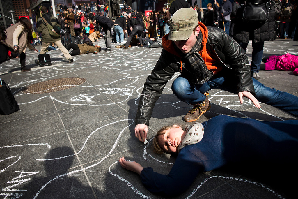 """. A woman is outlined in chalk while participating in a flash-mob that was  organized in support of stricter gun laws, in Times Square, New York, February, 24, 2013. The flash mob started with people raising their hands into the air, then crumpling to the ground; once lying on the ground, some participants acted dead while others pretended to check vital signs of those who were \""""dead,\"""" before outlining the \""""dead\"""" in chalk. REUTERS/Andrew Burton"""
