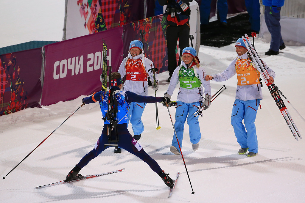 . Tora Berger of Norway, Tiril Eckhoff of Norway and Ole Einar Bjoerndalen of Norway run to congratulate Emil Hegle Svendsen of Norway after winning gold in the 2 x 6 km Women + 2 x 7 km Men Mixed Relay during day 12 of the Sochi 2014 Winter Olympics at Laura Cross-country Ski & Biathlon Center on February 19, 2014 in Sochi, Russia.  (Photo by Richard Heathcote/Getty Images)