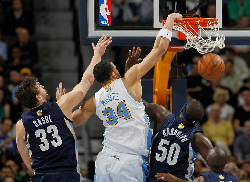 . Denver Nuggets forward JaVale McGee (34) dunks for a basket past Memphis Grizzlies center Marc Gasol (33), of Spain, and forwards Zach Randolph (50) and Quincy Pondexter in the first quarter of an NBA basketball game in Denver, Friday, March 15, 2013. (AP Photo/David Zalubowski)