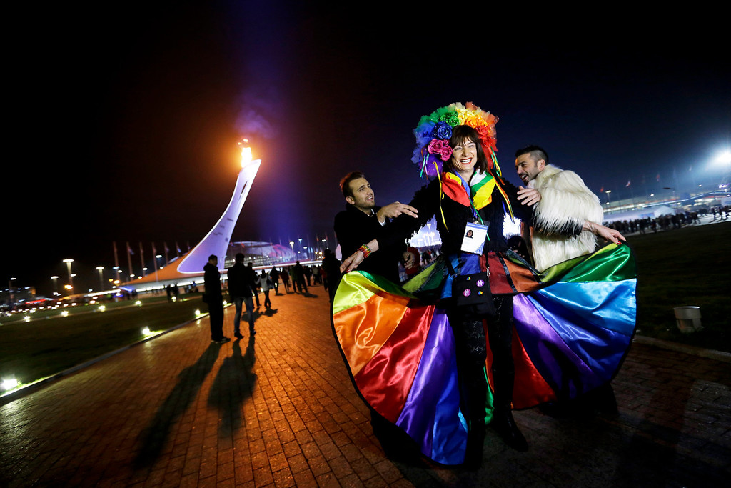 . Vladimir Luxuria, center, a former Communist lawmaker in the Italian parliament and prominent crusader for transgender rights, is led away by friends to attend a women\'s ice hockey match after posing for photos on the Olympic Plaza at the 2014 Winter Olympics, Monday, Feb. 17, 2014, in Sochi, Russia. Luxuria was soon after detained by police upon entering the Shayba Arena. (AP Photo/David Goldman)