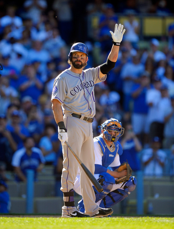 . Colorado Rockies\' Todd Helton acknowledges fans during his last at-bat as Los Angeles Dodgers catcher Tim Federowicz watches during the ninth inning of a baseball game, Sunday, Sept. 29, 2013, in Los Angeles. (AP Photo/Mark J. Terrill)