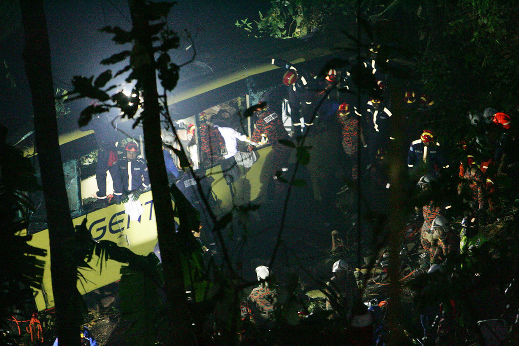 . Malaysian emergency services personnel search for passengers after a bus carrying tourists and local residents fell into a ravine near the Genting Highlands, about an hour\'s drive from Kuala Lumpur, Malaysia, Wednesday, Aug. 21, 2013.   (AP Photo)